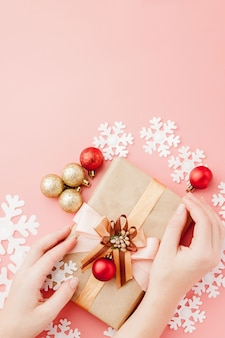 Female hands holding present with bow on pink . festive backdrop for holidays: birthday, valentines day, christmas, new year. flat lay