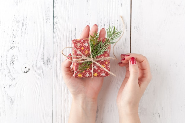 Female hands holding present with twine bow on white rustic background. festive backdrop for holidays: christmas, new year. flat lay style