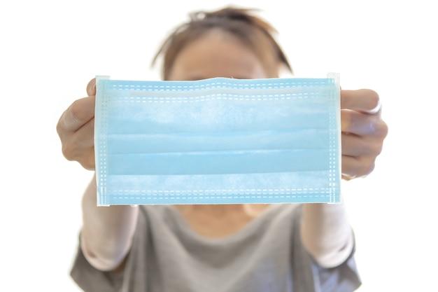 白い背景で隔離の保護フェイスマスクを保持している女性の手
