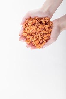 Mani femminili che tengono pasta a forma di cuore crudo su sfondo bianco. foto di alta qualità