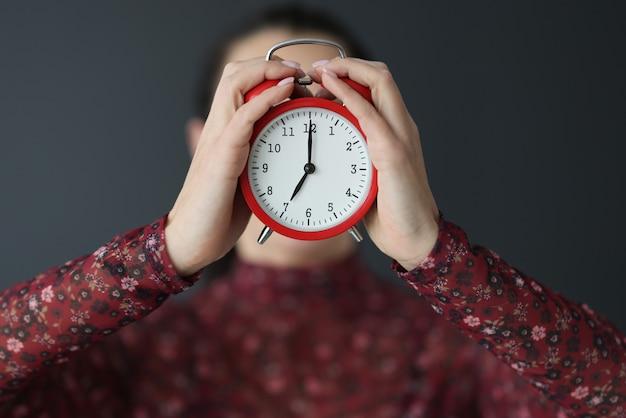 여성 손 얼굴 근접 촬영 앞 빨간색 알람 시계를 들고. 마감일 개념