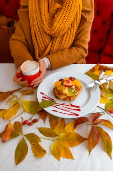 Женские руки держат красную чашку кофе возле осенних листьев торта