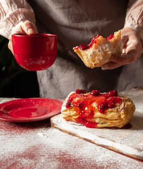 Female hands holding red cup of coffee and slice of puff staffed with plum or red currant jam on the table.