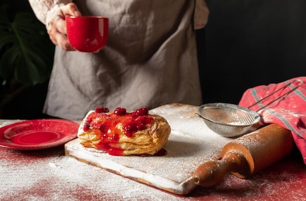 テーブルの上に梅または赤すぐりのジャムを配置したパフの近くでコーヒーの赤いカップを保持している女性の手。