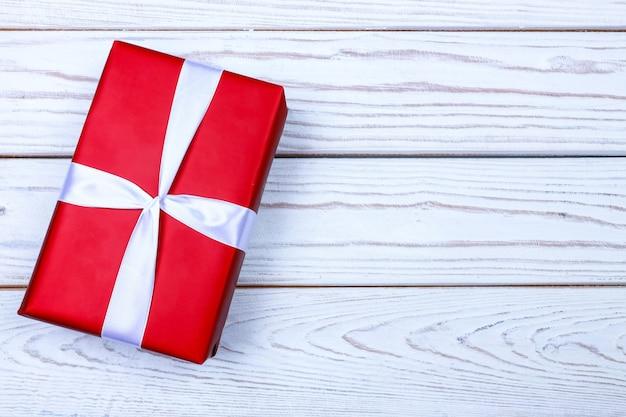 Женские руки держат красную подарочную коробку с лентой на деревянном фоне