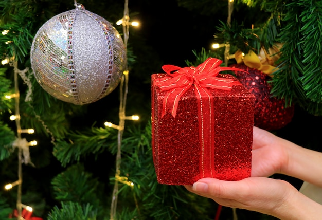 Female hands holding a red glitter gift box with silver sequined ball ornament