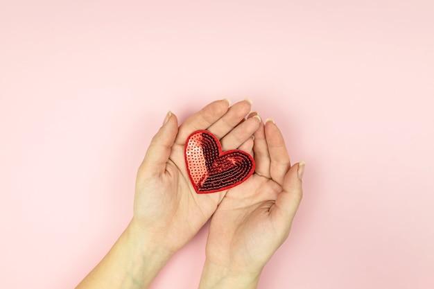 분홍색 배경에 빨간색 장식 조각이 마음을 잡고 여성 손. 복사 공간이있는 창의적인 최소 레이아웃.