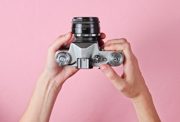 ピンクのレトロなフィルムカメラを保持している女性の手。