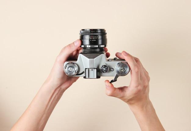 ベージュのレトロなフィルムカメラを保持している女性の手。