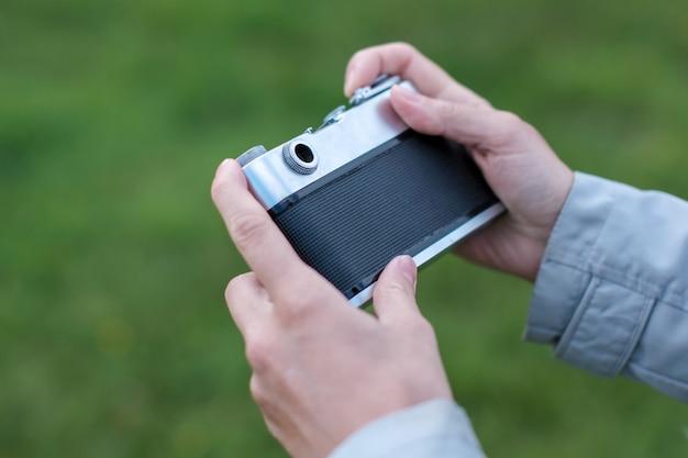 レトロな写真カメラを保持し、背景の草のスナップショットを撮る女性の手。