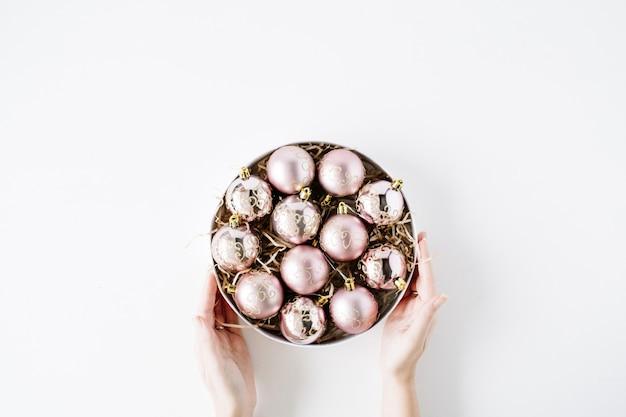 白い背景の上の明るいクリスマスボールと丸いボックスを保持している女性の手。フラットレイ、上面図