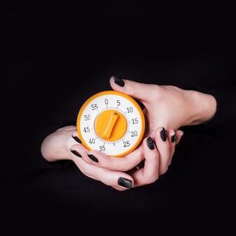 Женские руки, держа круглый оранжевый кухонный таймер на черном фоне, ожидание концепции времени