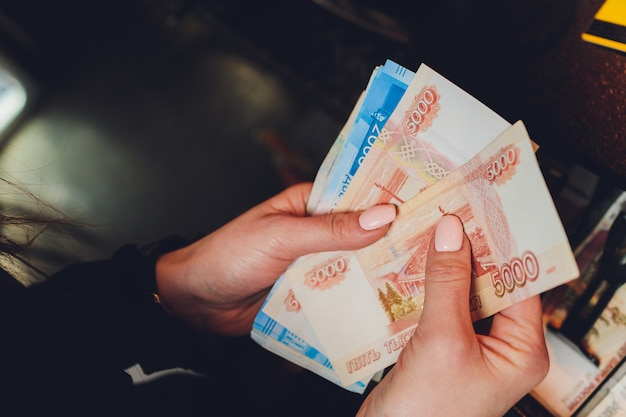 Female hands holding russian banknotes of one thousand rubles.