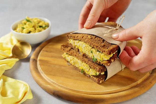 Женские руки держат бутерброды с веганским яичным салатом из тофу