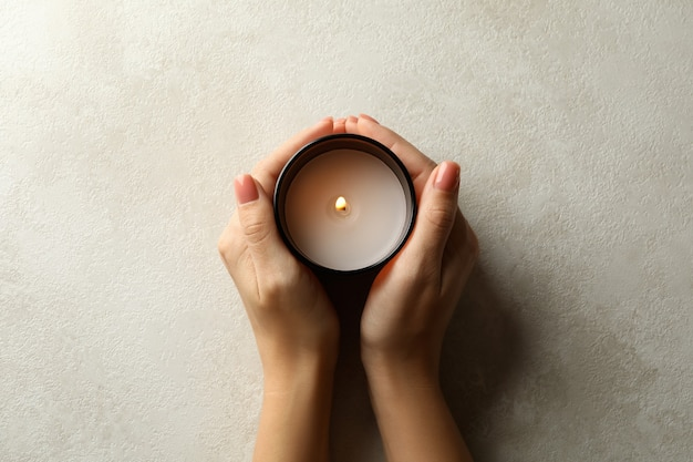 Женские руки держат ароматическую свечу, вид сверху