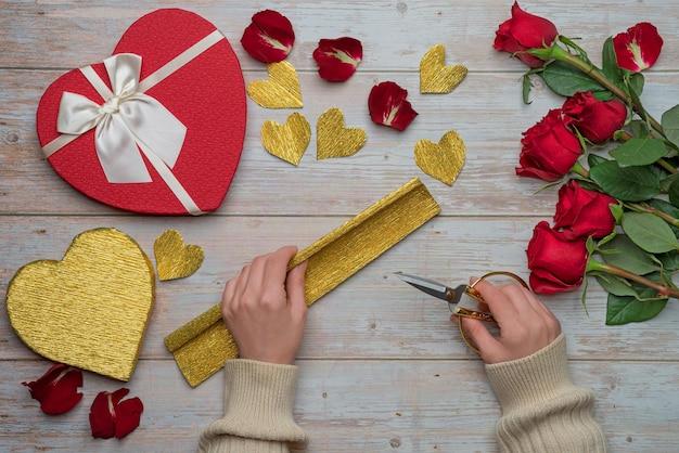 Female hands holding scissors creating gold foil packaging