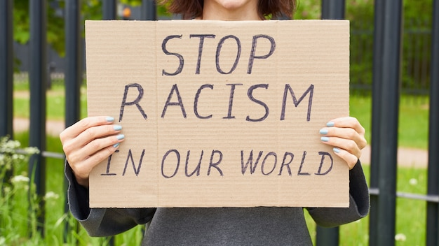 Female hands holding a sign about racism