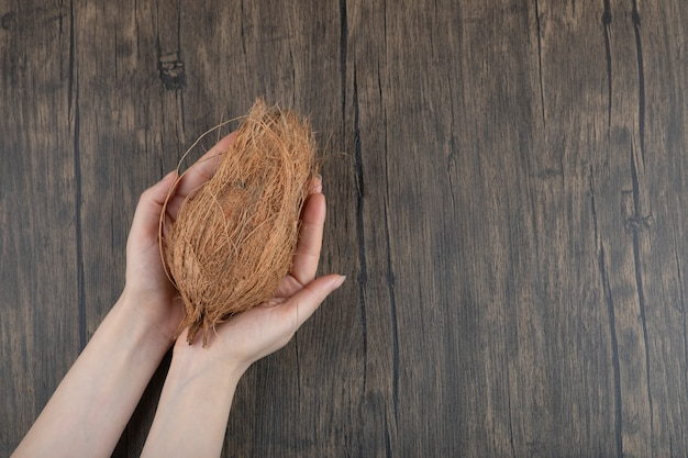 Female hands holding single ripe coconut on wooden surface