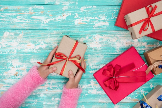 Mani femminili che tengono una piccola scatola con un regalo tra le decorazioni festive invernali su una vista da tavolo bianca. composizione piatta per compleanno, natale o matrimonio.