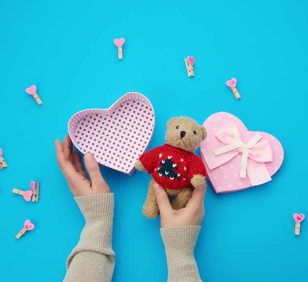Female hands holding a small brown teddy bear, on a blue background an open empty heart-shaped box