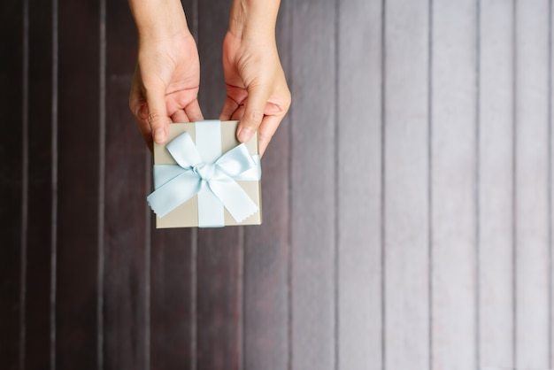 Female hands holding a small gift wrapped with blue ribbon on wooden background