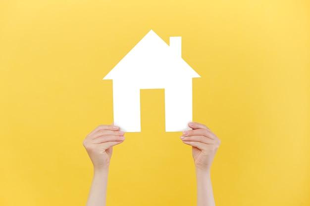 Женские руки держат маленький белый бумажный домик