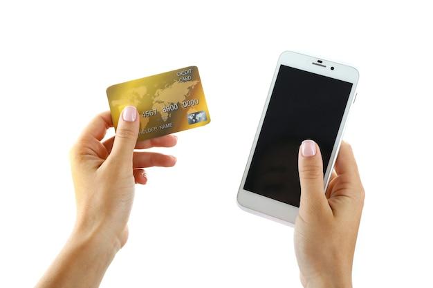 スマートフォンとクレジットカードを保持している女性の手、白で隔離