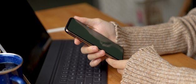 Female hands holding smartphone while sitting at workspace with digital tablet on wooden table