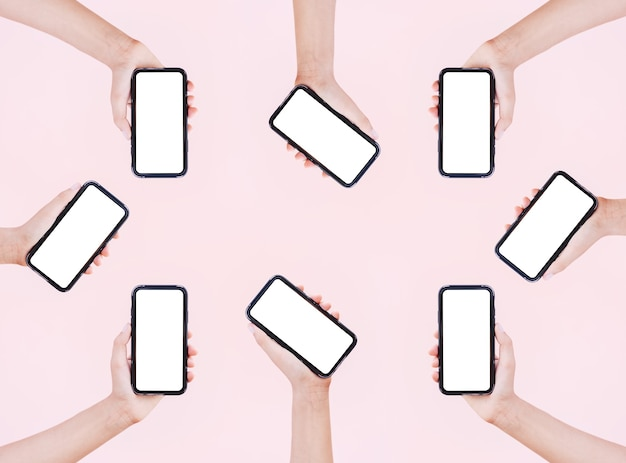 Female hands holding smartphones with mockup on surface of pastel pink color