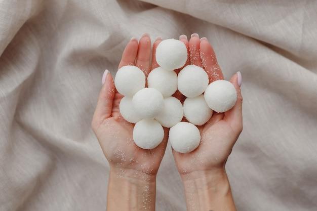 단단한 수제 천연 샴푸 또는 설탕 스크럽 공을 들고 있는 여성 손
