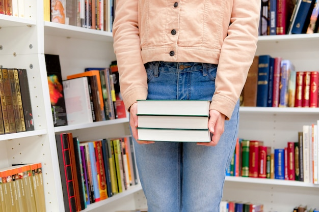 Female hands holding stack of books in shop on background of bookshelves. paper reading concept.