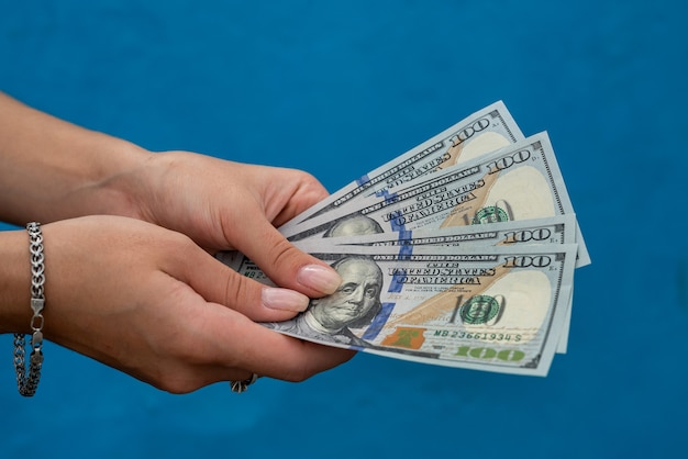 파란색 배경에 고립 된 돈의 스택을 들고 여성 손