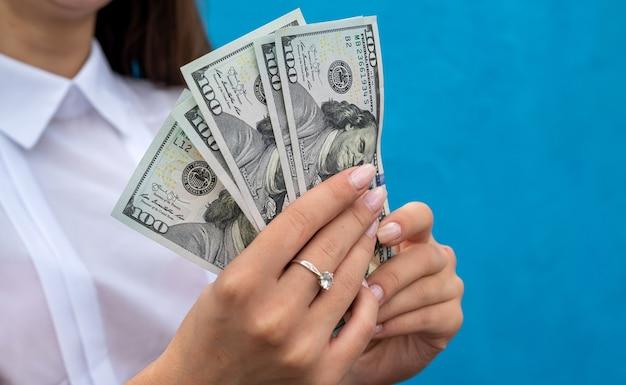 파란색 벽에 고립 된 돈의 스택을 들고 여성 손