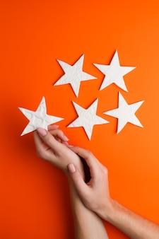 オレンジ色の背景に星型のチャイナ粘土を保持している女性の手