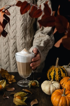 Female hands holding steaming cappuccino, latte coffee with pumpkins, autumn leaves on wooden table
