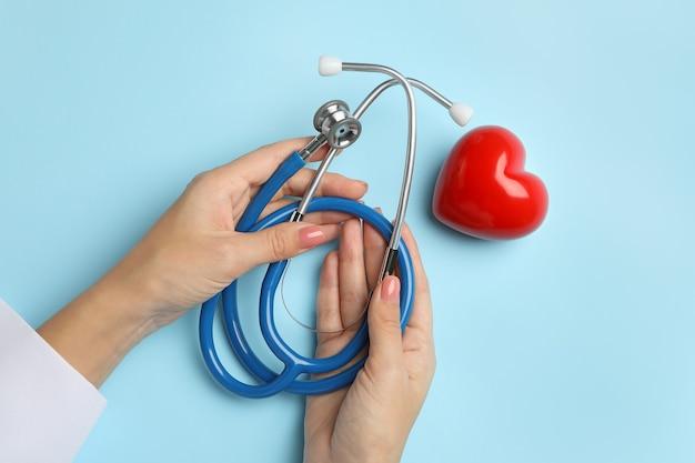 心と青に聴診器を保持している女性の手