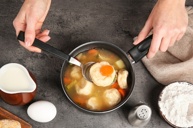 Female hands holding stewpan with delicious chicken and dumplings on kitchen table