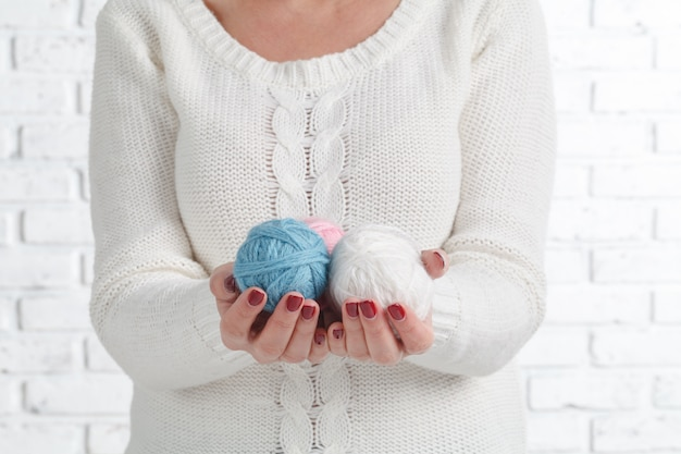 ステッチ、糸、糸を持っている女性の手をクローズアップ。手作りと手仕事のための材料