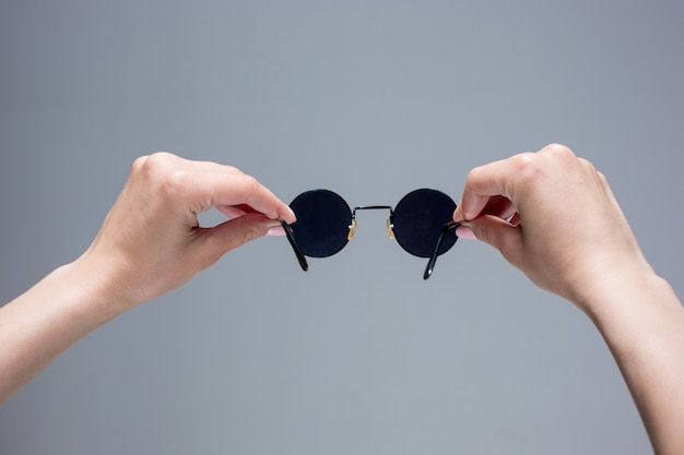 The female hands holding sunglasses on gray background.