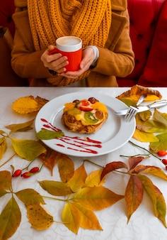 Женские руки держат красную чашку кофе возле торта на фоне осенних листьев