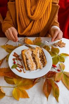 Женские руки, держа белую тарелку с тортом