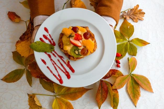 Женские руки держат белую тарелку с фруктовым пирогом