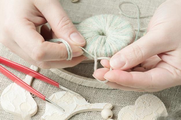 Female hands holding thread