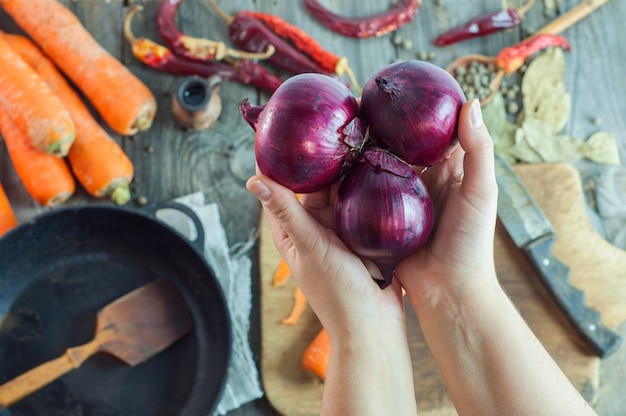 Female hands holding three red onions on the table with vegetables