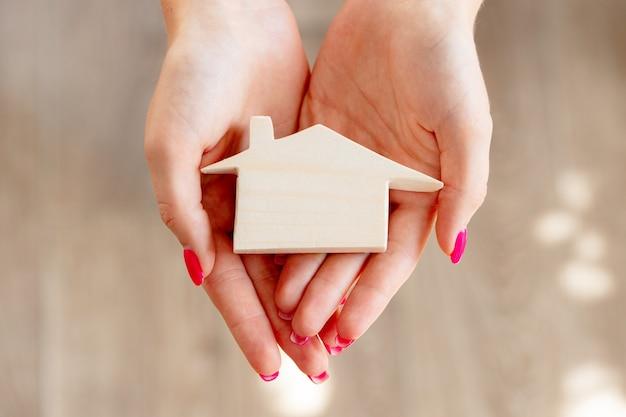 Женские руки держат игрушечный деревянный домик миниатюрный крупным планом