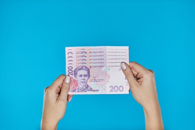 Female hands holding ukrainian banknotes on blue
