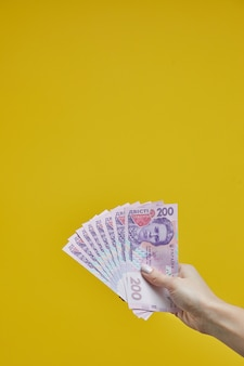 Female hands holding ukrainian banknotes on yellow