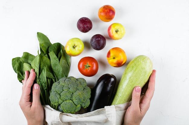 Female hands holding vegan vegetables, cotoon reusable bag on light table. zero waste, care concept