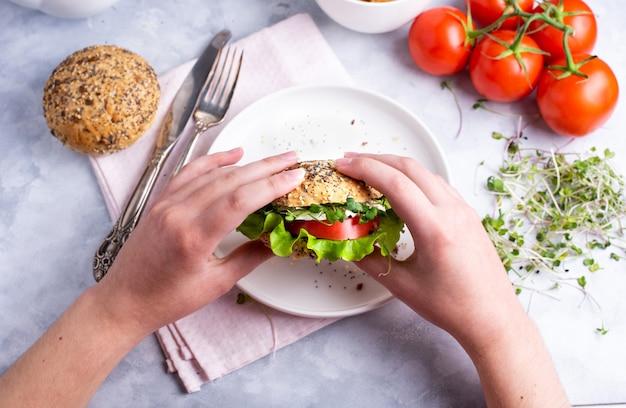 トマト、チーズ、レタス、マイクロニヤリと野菜のハンバーガーを保持している女性の手