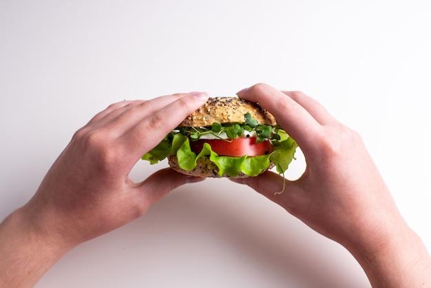 トマト、チーズ、レタス、マイクログリーンと野菜のハンバーガーを保持している女性の手